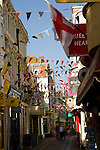 Flags and bunting cross a narrow street in Weymouth, Dorset, England