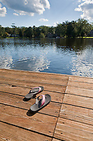 A pair of summer flip flops at the edge of a wooden dock on a public lake