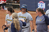 GREENSBORO, NC - MARCH 11: Kayleigh Willis #12 of UNC Greensboro celebrates her home run with teammates and coaches during a game between Northern Illinois and UNC Greensboro at UNCG Softball Stadium on March 11, 2020 in Greensboro, North Carolina.