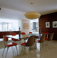 A George Nelson pendant light hangs over the glass-topped dining table which is surrounded by red Eames chairs