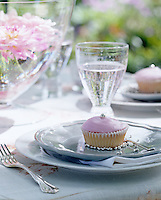 Detail of a cupcake with pink icing on a plate at an outdoor summer tea party
