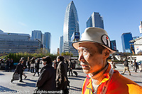 Seichi Namasu works as a volunteer tourist guide in Shinjuku, Tokyo, Japan. Friday December 9th 2016. In preparation for the 2020 Tokyo Olympics and to aid the increasing number of tourists visiting the country tourists guides organised by the Tokyo Government volunteer to provide multi-lingual information at popular destinations around the capital
