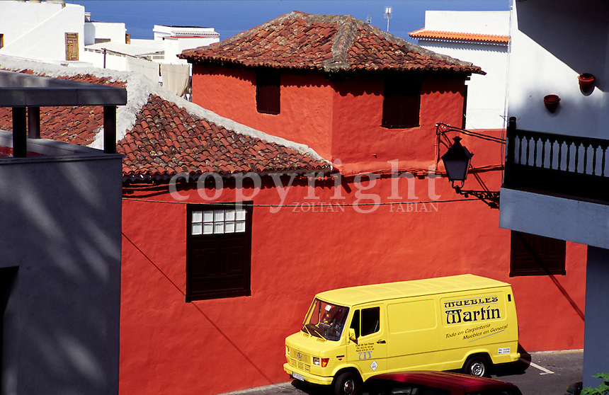 Yellow van parking next to a red wall in the street in Icod de los Vinos, Tenerife, Canary Islands, Spain, Europe