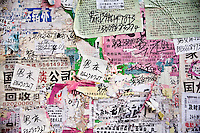 Advertisements and leaflets cover a bulletin board in Haerbin, Heilongjiang, China.