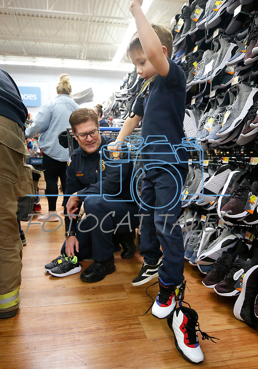 Dante gives a pair of shoes a jump test while shopping with Carson City Fire Chief Sean Slamon during the 16th annual Holiday With a Hero shopping day, in Carson City, Nev., on Wednesday, Dec. 18, 2019. The event pairs law enforcement, fire, military and medical officials with homeless children from the Carson City School District McKinney-Vento program for a $100 shopping spree at Walmart.<br /> Photo by Cathleen Allison