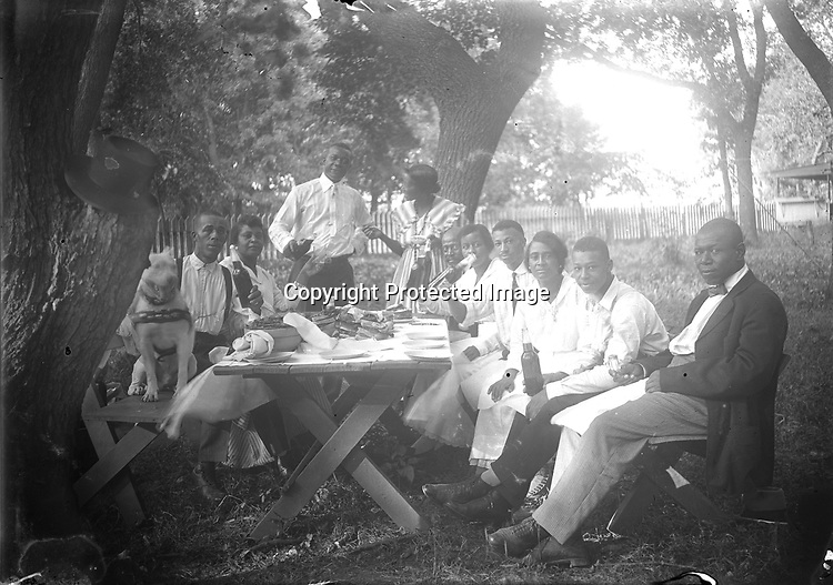 BACKYARD PICNIC. In a backyard enclosed with a picket fence, 10 picnickers (and one pit bull terrier) pause for a toast before their meal. The scene appears casual, but the picnic benches have been angled out from the table to allow each person to be seen, and to lead the eye to the couple serving as host and hostess<br /> <br /> Photographs taken on black and white glass negatives by African American photographer(s) John Johnson and Earl McWilliams from 1910 to 1925 in Lincoln, Nebraska. Douglas Keister has 280 5x7 glass negatives taken by these photographers. Larger scans available on request.