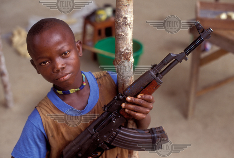 © Giacomo Pirozzi / Panos Pictures..SIERRA LEONE..Child soldier brandishing his rifle.