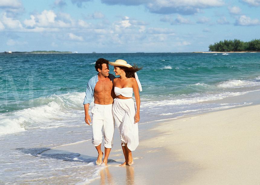 Couple in white walking on beach