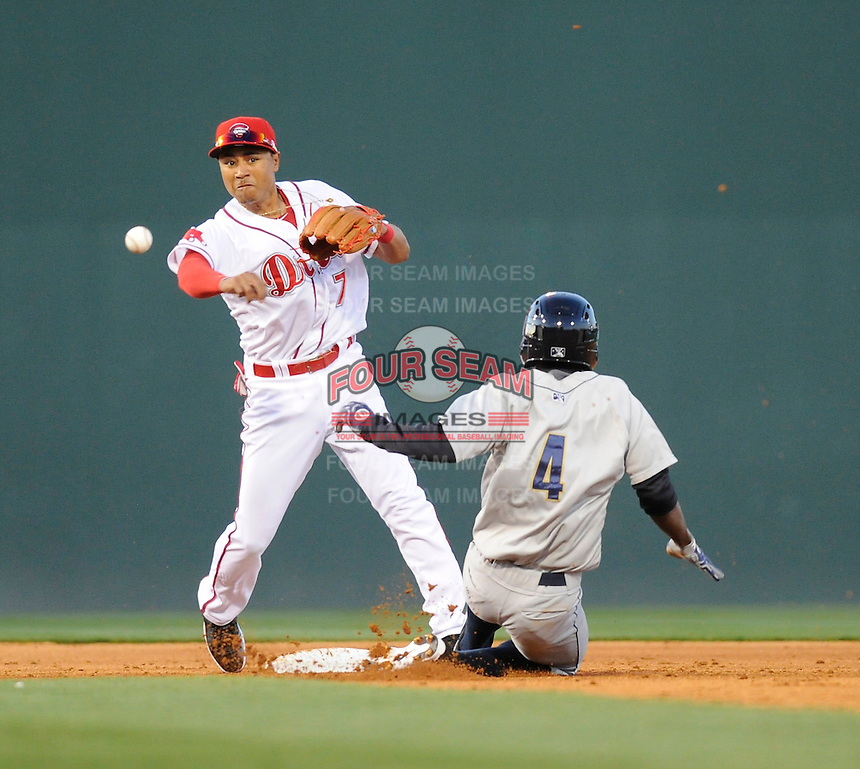 Infielder Claudio Custodio (4) of the Charleston River Dogs is out at second base as infielder Mookie Betts (7) of the Greenville Drive turns a double play during the third inning of a game on Opening Day, Friday, April 5, 2013, at Fluor Field at the West End in Greenville, South Carolina. The Drive won, 4-2. (Tom Priddy/Four Seam Images)