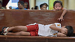 A girl reaches over a pew toward a sleeping boy in Knox United Methodist Church in Manila, Philippines.