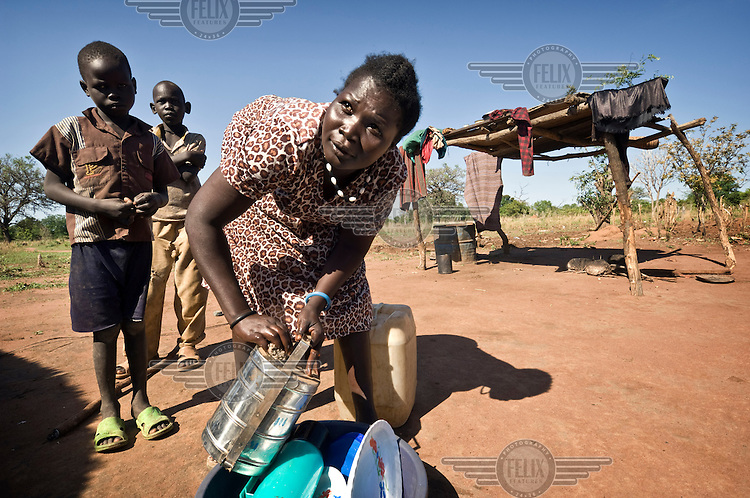 A woman washes dishes at her home in Tali Payam. Central Equatoria, South Sudan.