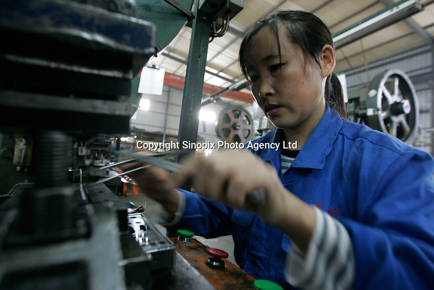 Women at a factory in Shenzhen press various metal parts for assembly.