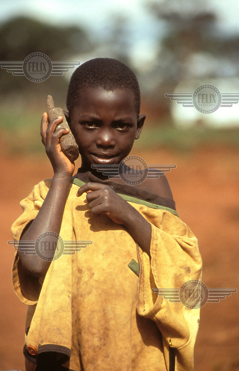 Rwandan refugee boy with a mud mobile telephone, emulating the aid workers.