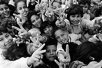 "State of Palestine. West Bank. Balata Camp. Palestinian refugees. Schoolgirls making V signs in UNRWA (United Nations Relief and Works Agency for Palestine Refugees in the Near East) schoolyard. The V sign is a hand gesture in which the index and middle fingers are raised and parted, while the other fingers are clenched. It has been used to represent the letter ""V"" as in ""victory"". Balata Camp is a Palestinian refugee camp established in the northern West Bank in 1950, adjacent to the city of Nablus. It is the largest refugee camp in the West Bank. Balata Camp is densely populated with 30,000 residents in an area of 0.25 square kilometers. In 1991, Balata Camp was living under Isreal's occupation and rules as part as the Occuppied Territories. In the 1980s and 1990s, Balata residents played a leading role in the uprisings known as the First Intifada and the Second Intifada. Balata Camp is since 1993 under palestinian authority, located in the A zone. The Palestinian National Authority (PA or PNA) was the interim self-government body established to govern Areas A and B of the West Bank as a consequence of the 1993 Oslo Accords. Following elections in 2006, its authority had extended only in areas A and B of the West Bank. Since January 2013, the Fatah-controlled Palestinian Authority uses the name State of Palestine on official documents. T © 1991 Didier Ruef"