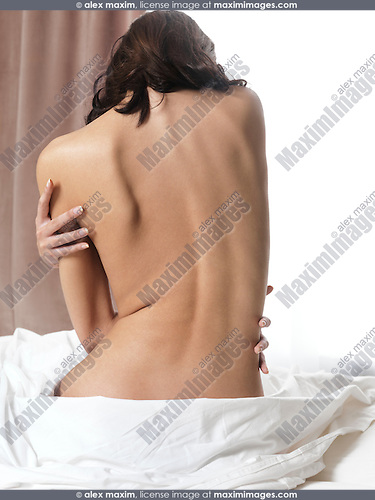 Nude young woman sitting on a bed close up of bare back in front of a brightly lit window