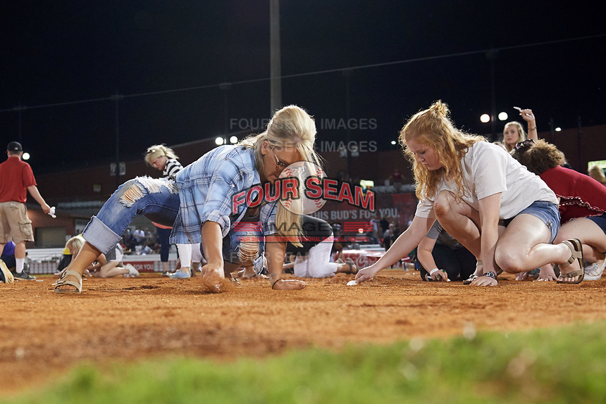 """Arkansas Travelers female fans search the infield for a buried diamond ring during the teams annual """"Diamond Dig"""", presented by Lee Ann's Fine Jewelry, after a game against the Midland RockHounds on May 25, 2017 at Dickey-Stephens Park in Little Rock, Arkansas.  Midland defeated Arkansas 8-1.  (Mike Janes/Four Seam Images)"""
