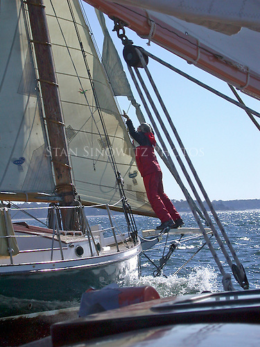 The roller furling jib is stuck and the man is standing on the bowspirit of the Friendship sloop trying to correct it.