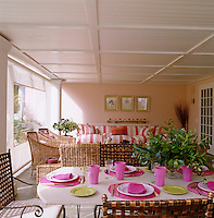 The porch is a living/dining area screened from the garden by a blind and furnished with cane and wrought-iron chairs