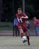 Harvard University defender Ross Friedman (4) passes the ball. Boston College (white) defeated Harvard University (crimson), 3-2, at Newton Campus Field, on October 22, 2013.