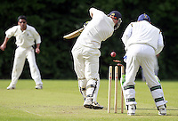 Ben Sudell of Highgate is bowled by Kamlesh Desai (L) during the ECB Middlesex Division Three game between Highgate and Harrow Town at Park Road, Crouch End on Saturday May 24, 2014
