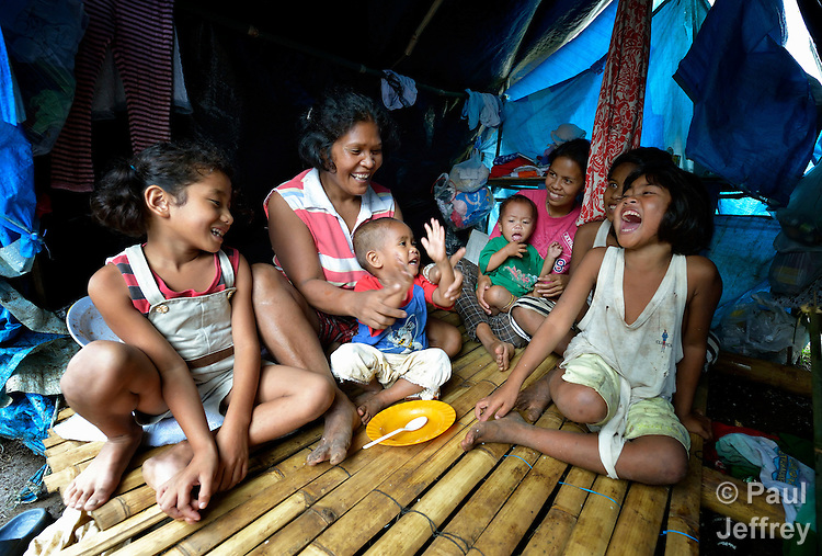 Sharon Liguyon, 44, enjoys a moment with her children inside their temporary home. They are part of a group of almost 200 residents of the indigenous village of San Fernando who fled their home on March 14, 2012, shortly after the March 5 assassination of her husband Jimmy Liguyon, the baranguay captain. Mr. Liguyon was killed by a paramilitary squad led by Aldy Salusad, which was angered by Liguyon's refusal to sign papers ceding the community's land to a large mining company. Convinced they were also in danger from Salusad and his military allies, his widow and other community members fled to the provincial capital of Malaybalay, where they have set up temporary shelters on the grass in front of provincial offices. They promise not to leave until there is justice in the killing of Liguyon..