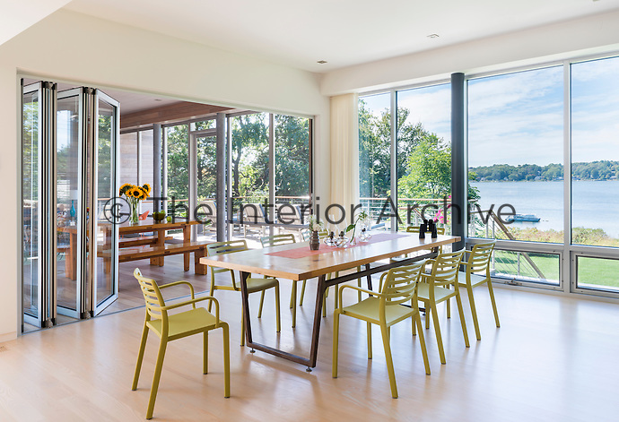 A modern, light and airy dining room with a stained ash wood floor and full height picture windows. A set of folding glass doors leads through to a dining area beyond, which allows access to a balcony terrace. The room is furnished with a wood and metal table and green dining chairs.