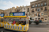 Malta, 28 December 2014<br /> <br /> Along the West shore of the old city of Valetta. A lot of old badly maintained houses. Tourist mini bus passing by with advertisement for the National Aquarium.<br /> <br /> Photo Kees Metselaar