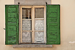 Window with green shudders and a traditional handmade lace curtains in the small town of Borgonovo in the Bregaglia Valley of Switzerland, below St. Moritz