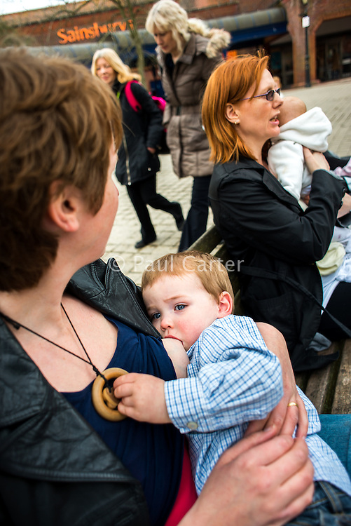 Women sitting on benches in the precinct outside a supermarket. One is breastfeeding her toddler.<br /> <br /> Image from the &quot;We Do It In Public&quot; documentary photography project collection: <br />  www.breastfeedinginpublic.co.uk<br /> <br /> Dorset, England, UK<br /> 17/04/2013