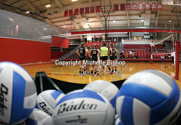 The University of Nebraska-Omaha volleyball team huddles before a scrimmage against the alumni team at the Sapp Fieldhouse. (Photo by Michelle Bishop)  .