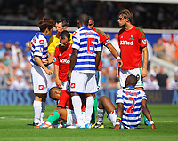FAO SPORTS PICTURE DESK<br /> Pictured: Wayne Routedge of Swansea (3rd L) is getting up from the ground after being injured. Saturday 18 August 2012<br /> Re: Barclay's Premier League, Queens Park Rangers v Swansea City FC at Loftus Road Stadium, London, UK.