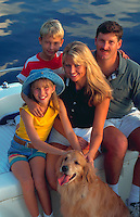 Portrait of family in boat with their golden retiever.