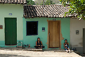 Goias Velho, Brazil. Well preserved colonial town; colonial architecture; two smiling girls sitting on the pavement outside a small house.