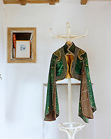 A green velvet bolero jacket with long flowing sleeves is edged with looping embroidery and yellow spots