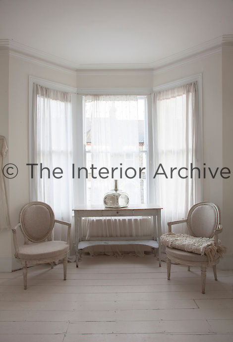 The bay window of the guest bedroom is flanked by a pair of antique French chairs upholstered in a restrained cream