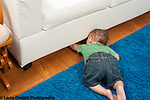 10 month old baby boy searching for toy that rolled under couch object permanence