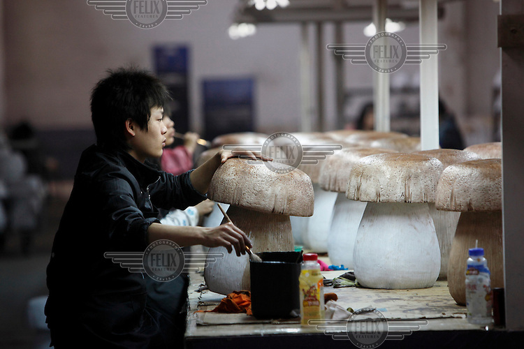 A worker paints a novelty garden mushroom decoration, made from petroleum resin (C9), at the Chuan Sen Art & Design Factory on the outskirts of Guangzhou.