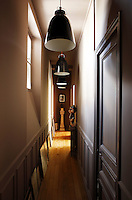 A long corridor is lit by a series of black-lacquered pendant lights
