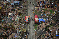 Survivors of Typhoon Haiyan wave as a U.S. military helicopter delivering aid flies over their isolated village north of Tacloban November 17, 2013. Mobbed by hungry villagers, U.S. military helicopters dropped desperately needed aid into remote areas of the typhoon-ravaged central Philippines, as survivors of the disaster flocked to ruined churches on Sunday to pray for their uncertain future. The Philippines is facing up to an enormous rebuilding task from Typhoon Haiyan, which killed at least 3,681 people and left 1,186 missing, with many isolated communities yet to receive significant aid despite a massive international relief effort.