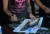 Oct. 27, 2012; Las Vegas, NV, USA: NHRA funny car driver Alexis DeJoria autographs a piece of Kenny Youngblood's artwork during qualifying for the Big O Tires Nationals at The Strip in Las Vegas. Mandatory Credit: Mark J. Rebilas-