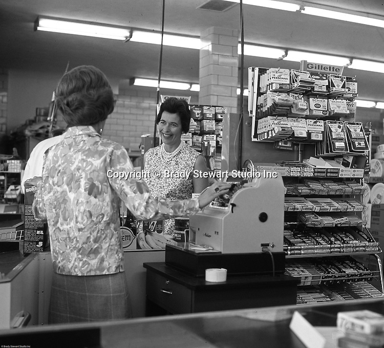 """Bethel Park PA:  View of a woman at the check out counter of Bethel Market Grocery Store.  Marjorie Stewart is being checked out by Millie during an onsite photography assignment for Bethel Market.  Bethel Market was """"the"""" grocery store in Bethel Park from the late 1950s through the early 1980s."""