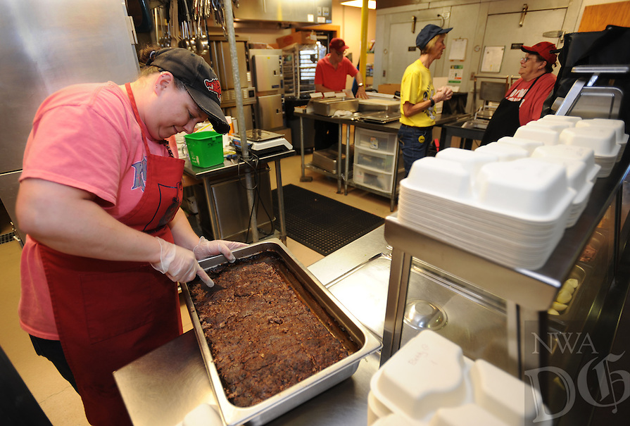 NWA Democrat-Gazette/ANDY SHUPE<br /> Deanna Allen, kitchen assistant at the Fayetteville Senior Activity and Wellness Center, slices a pan of meatloaf Friday, April 22, 2016, while preparing for the noon meal at the center. The center plans an expansion of its kitchen to keep up with the increase in the number of residents for whom they prepare meals.