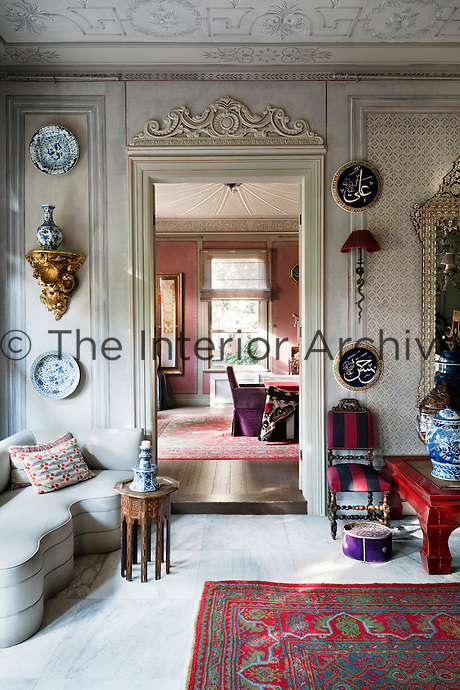 In the entrance of the reception room, there is a 19th century gilded shelf, an Ushak carpet and Arabic calligraphy ceramic plates. The layers of colours, patterns and textures add to the opulent feel of the room.