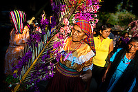 """A Salvadoran woman carries a palm branch with colorful flower blooms during the procession of the Flower & Palm Festival in Panchimalco, El Salvador, 8 May 2011. On the first Sunday of May, the small town of Panchimalco, lying close to San Salvador, celebrates its two patron saints with a spectacular festivity, known as """"Fiesta de las Flores y Palmas"""". The origin of this event comes from pre-Columbian Maya culture and used to commemorate the start of the rainy season. Women strip the palm branches and skewer flower blooms on them to create large colorful decoration. In the afternoon procession, lead by a male dance group performing a religious dance-drama inspired by the Spanish Reconquest, large altars adorned with flowers are slowly carried by women, dressed in typical costumes, through the steep streets of the town."""