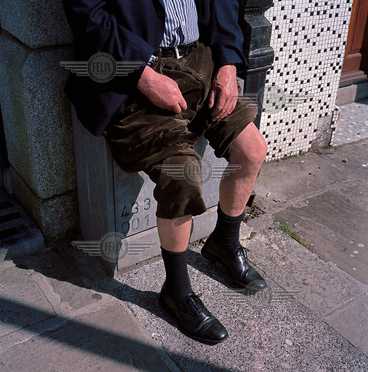 A man rolls up his trousers to expose his knees while enjoying the sunshine.