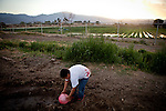 Nine-year-old Anthony Parra reaches for a ball in mud contaminated by raw sewage from the Rancho Garcia trailer park and agricultural fertilizers in Thermal, Calif., March 8, 2012.