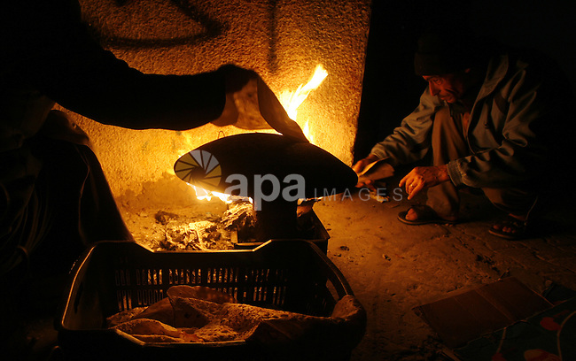 Palestinians prepare freshly baked pita bread at a traditional bakery using a wood burning stove in the Rafah refugee camp in the southern Gaza Strip on March 31, 2012. Gaza is experiencing a major electricity crisis because of a shortage of fuel for the power plant. Photo by Eyad Al Baba