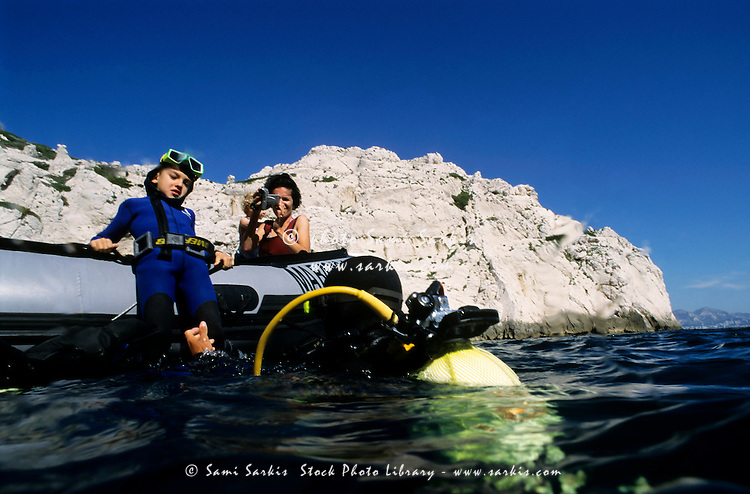 France marseille frioul island first dive of a young boy with his diver instructor filmed by his mother on the boat