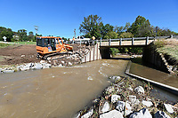 NWA Democrat-Gazette/SPENCER TIREY  A road crew works Monday, Oct. 7 2019, to repair the ground beside a bridge on west Lancashire Blvd. in Bella Vista where water damaged it during the flooding from Sunday's storm.