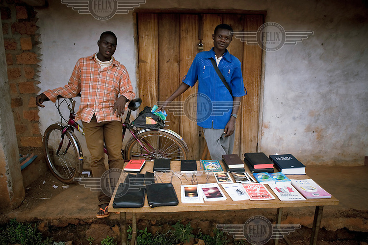 In Bangassou, two men lean on a bicycle next to a stall where French language bibles, glasses and Christian books are for sale.